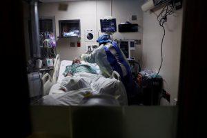 Медсестра ввела глубокую всасывающую трубку в легкие больного коронавирусом в отделении реанимации в Чикаго